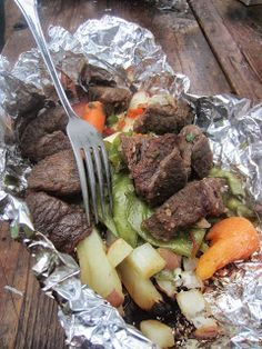 Tin foil dinner recipe for #camping. Put ingredients like beef, potatoes green onions, carrots and peas in tin foil pouch, add spices and toss it on the coals. #campingrecipes