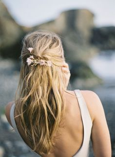 Half up hairstyle with pretty wild flowers tucked in.