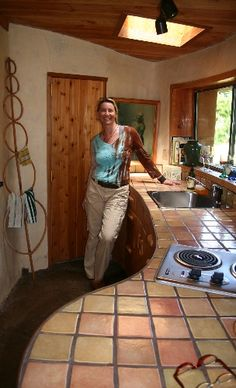 Nicole in an adobe kitchen interior of a Cob House on Mayne Island, photo by Monica Holy for 'Middle Earth Home'
