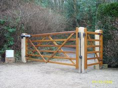 Wooden automated driveway gate with side pedestrian gate.