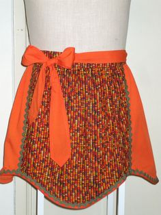 Orange you glad its almost time for Thanksgiving? This Half-Apron has a corn cob printed waistband & center panel w/Orange side panels and waist ties. The three panels are trimmed with Olive rick rack and Orange bias trim. The waist is 25 inches across, the waist ties are 38 inches long each, able to be tied in back or wrap around to the front. The apron is 17 long from waistband to hem.  Corn cob print is cotton, the Orange solid fabric is a cotton/polyester blend. All fabrics...
