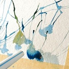 Make some fun abstract art by blowing watercolors on paper with a straw.