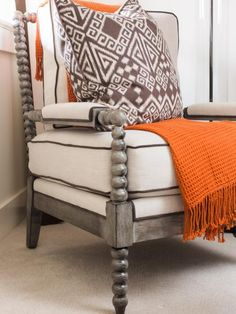 The bedroom's carved wood and upholstered bobbin chair is paired with a weaved orange throw and ethnic print pillow for extra comfort and warmth.
