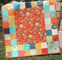 "This quilt was made with Block Party by Sandy Gervais by Moda Fabrics. This beautiful quilt includes red, orange, yellow, cream, navy blue, aqua and green. It measures approximately 38"" by 43"" perfect for that special little girl to cuddle with. The backing is a coordinating print"