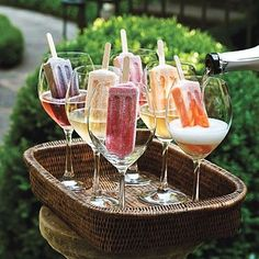 Well this is fun!    A new trend is to place popsicles in glasses and pour champagne on top.  The popsicle slowly melts into the alcohol and provides a super sweet taste.  This would be an awesome signature drink at weddings and parties!  The drinks can be easily coordinated to specific colors and/or flavors.