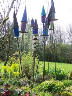 The tops of her bird houses are made from copper or galvanized metal sheets rolled into a cone shape like the Tin Man's hat from the Wizard Oz. The body of the house is made from different sized metal flower buckets and the base comes from unique trays, usually found at the Goodwill.