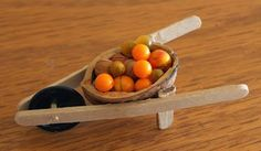 Fairy garden wheelbarrow with pumpkins *walnut shell and button?   So cute!