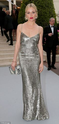 Golden girl: Sienna Miller looked fabulous in a shimmering gown that featured spaghetti st...