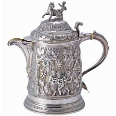 English Silver Cider Jug  Marks effaced, 19th century  The finial in the form of a putto, above a curved spout and continuous bacchanalian scene, on a circular foot.