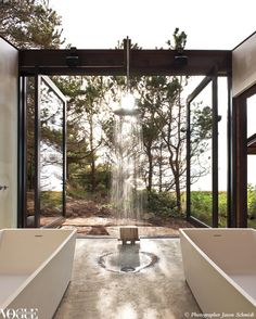 Modern open air outdoor bathroom inspiration. Dual bathtubs, shower with floor drain, large doors and windows that open to expose fresh air and a breathtaking landscape view.
