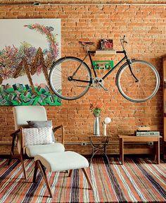 A parede de tijolos aparentes recebeu quadro e mais um complemento: uma bicicleta. Ela fica suspensa por uma prateleira de madeira própria. Produção de Juliana Pickel