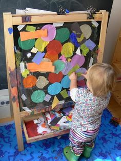 On the second easel I taped a piece of clear contact paper (sticky side out) for the base of the collage. Then I filled the tray with materials such as paper, cotton balls, and feathers and showed the children how they stick to the paper.