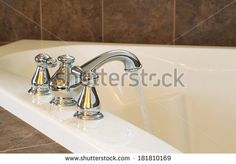 Horizontal photo of chrome faucet running water into soaking tub in master bathroom