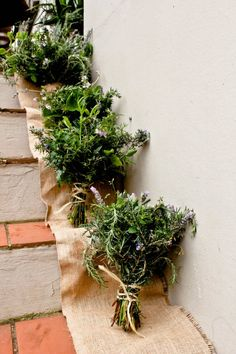 Rosemary, lavender, and  other herb bouquets displayed on a burlap runner. Beautiful and unusual presentation. ♥