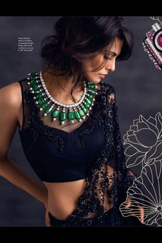 sultry in black saree and green necklace