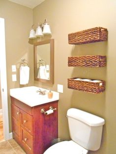 Cheap wicker baskets nailed directly to the wall for additional storage above-the-toilet! Functions as both deco and toiletries storage. | herothhome.com