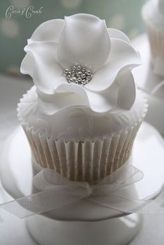 The flower is made with rounds of fondant/gumpaste that have been ruffled then put together with edible glue and then silver dragees are put in the center with more edible glue.