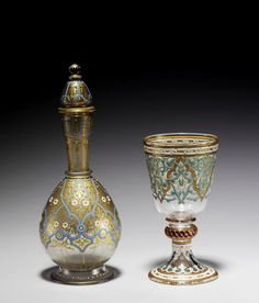 Two small enamelled glass vessels   by J.& L. Lobmeyer, Vienna, and Brocard, Paris, late 19th Century  the Lobmeyer decanter bottle, decorated in opaque white and light blue and gilt with arabesque and floral motif, signed 'Lobmeyer' on base, the Brocard glass decorated in opaque white and turquoise-blue, and red enamel, also with gilt stylised arabesque motif, signed 'Brocard' on foot   the larger 16 cm. high