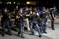 Police officers work to keep order as demonstrators express their feelings on August 18, 2014 in Ferguson, Missouri. Violent outbreaks have taken place in Ferguson since the shooting death of unarmed teenager Michael Brown by a Ferguson police officer on August 9th. (Photo by Joe Raedle/Getty Images)