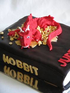this is a gluten free chocolate cake with butter cream and then decorated with fondant too be a book.then smaug is with his treasure on top of the book.Smaug is made of fondant . Hobbit Cake, Hobbit Party, Make A Dragon, Gluten Free Chocolate Cake, Dragon Cakes, Fantasy Movies, Awesome Cakes, The Hobbit, Cake Designs