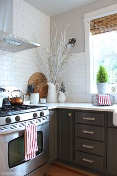 Gray cabinets, stainless stove, light greige walls, white subway tile - this is what my kitchen will look like!