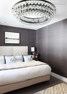 Feature glamorous lighting. Whether it's a ceiling fixture, table lamps or pendants, statement lighting amps up the luxury factor. You might choose a fixture or lamp with a shiny finish — perhaps gold, glass or crystals. Selecting one with a large or unusual shape can also help the room look more upscale. I think of statement lighting as room jewelry that instantly adds sparkle and glamour to an ordinary bedroom.