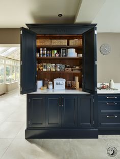 The pantry features bi-fold doors and a marble shelf to help keep some food items cool. The walnut internals compliment the dark blue cabinetry beautifully,