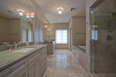 Sumptuous master bath offers separate mirrored vanities with under mount sinks, Ultra Bain jetted tub plus separate shower, gorgeous Verde Laura slab granite counter tops with chrome sconces / plumbing hardware and recessed lighting.