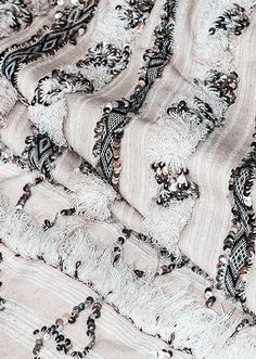 Often known as the Moroccan Wedding blankets, handiras are traditionally worn by Berber women as ceremonial capes. These gorgeous handwoven ivory wool and cotton textiles are artistically embellished with silver sequins in patterns to symbolize tribe, family and name.