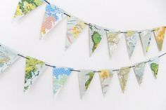 Map bunting by PeonyandThistle via Etsy. Flags are made from colorful world maps. #buntings #maps #weddingdecor