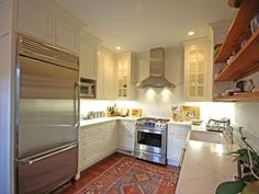 Bright white kitchen, stainless steel and a tribal rug. The perfect kitchen