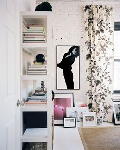 pretty and casual-- white painted brick wall, layered framed art, black and white floral curtains