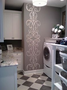 An Architectural Border Masking Stencil, adds an enlarged pattern vertically on the laundry room's prominent wall. A loose pattern or a singular stencil placed perfectly enhances the overall design of a room.