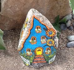 Complete with picket fence and flower garden, this miniature painted rock house is bright, colorful, and will perk up any dull garden area.  It is painted on a rock of hard composition, so it can withstand outdoor elements better than most painted rocks, although no painted rock can take excessive moisture and direct sunlight forever, if you want to keep it in your garden, it is recommended to give it an extra coating of clear acrylic from time to time for extra durability.  3 1/2 tall, by…