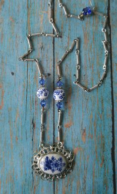 Vintage Components:  Porcelain brooch  Silver link chain  Blue crystal clasp  Silver bead caps  Non Vintage Components:  Blue Swarovski crystal beads  Glass flower beads  20ga wire  chainmaille jump rings  length 22