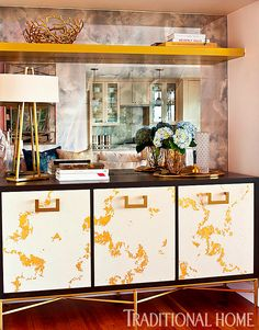 Gold-leaf detailing on the storage console adds a textured element. - Photo: Michael Garland / Design: Shannon Wollack and Brittany Zwickl