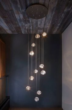 Lake Tahoe Residence by Chelsea Sachs Design | Mizu glass pendants by Terzani in the foyer to mimic the rippling water found in the creek behind the house.