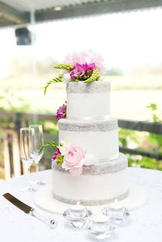 Three tiered white wedding cake with silver sugar detail and fresh flowers. Photo courtesy MMG Photography,