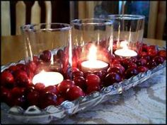 Maybe a gold charger plate with cranberries on it and a candle in the center like this.