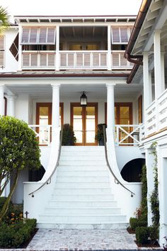 A curved entry staircase is a traditional design element in British Colonial architecture and steps up to a formal living room dressed in shades of white. Charleston Home By Beau Clowney of Beau Clowney Design