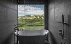 In this modern bathroom, a freestanding bathtub sits in front of another large window that perfectly frames the surrounding landscape. #ModernBathroom #Window