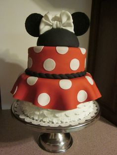Interpretive Minnie Mouse Bride cake made for a Disney destination wedding. Lower tier has 4 rows of ruffles overlayed with fondant skirt. Mouse ears include white bow and veil.