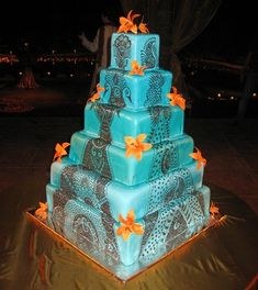 Mehandi Decorated Wedding cake  6 Tier square wedding cake with Turquoise blue spray and chocolate mehandi decorated. Orange lily was arranged around just added for looks.