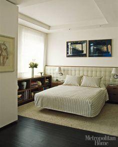 The master bedroom features walnut millwork and a room-wide upholstered headboard under art by Sarah Davis.   - ELLEDecor.com