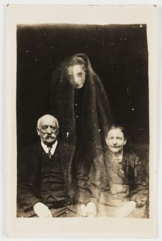 Spirit photography by paranormal investigator William Hope (1863–1933), who used multiple exposure techniques to render the appearance of ghost. A young woman's face appears as if floating above the sitters, draped in a cloak. Hope may have already held her photograph in his studio, or he may have asked the couple to supply photographs of deceased relatives under the pretense of using the image to contact the spirit world.