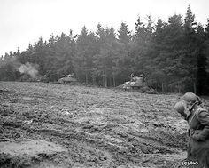 Sherman tanks mounted with 105-mm. howitzers open fire in a muddy field amid the Hürtgen Forest on November 17, 1944.