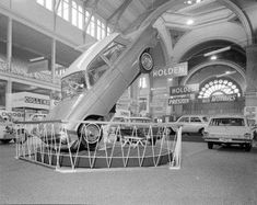 Photograph of a Holden motor car displayed upright on its front wheels, at an International Motor Show held in the Exhibition Buildings.