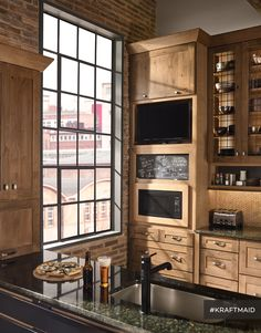 It's easy to grab a quick meal while watching TV, and the kitchen messaging center is in a can't-miss spot for clear communication. (Rustic Alder cabinets in Husk Suede)