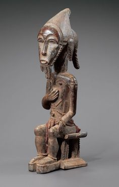 Statue usu asia . Baule, Ivory Coast. Wood, fabric pearls and pigments, h. : 40 cm. Private collection. © Muséee archives Dapper and Hugues Dubois