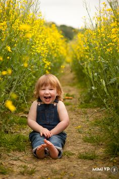 Girl laughing sat in field of rapeseed